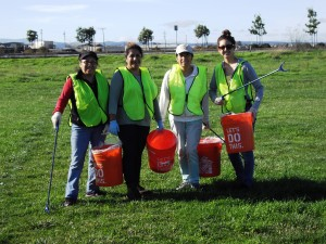 Four people cleaning up soccer field